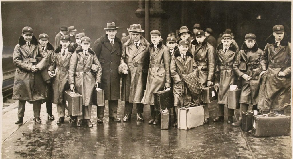 Dean A.V. Baillie, Mr Fred Ney and the choir boys of Westminster Abbey on a train platform in Canada, February 1927.