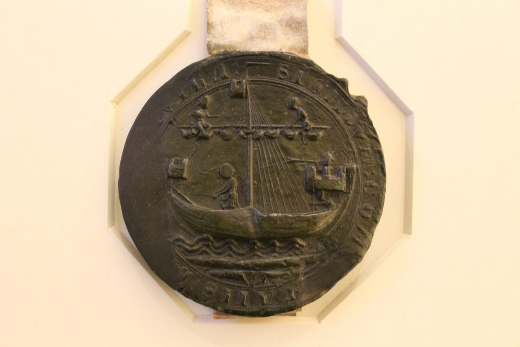 green wax seal showing ship and three sailors