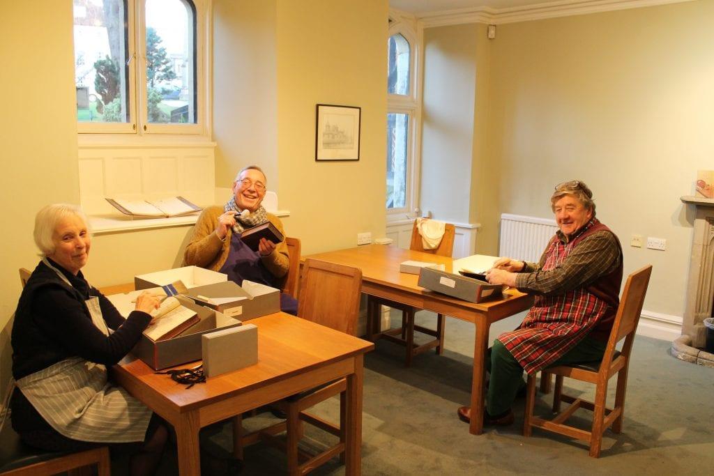 Volunteers dusting books